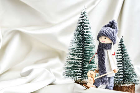 Christmas composition with doll skiing and fir trees festive decorations on silk. Christmas or New Year greeting card. Copy space. Trendy champagne color