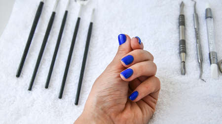 Manicure - tools for creating, gel polishes, all for the treatment of nails, the concept of beauty, care on white towel background. Banner for inscription salon. Copy space for text.