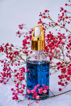 Glass dropper of cosmetic oil and dried flowers and herbs on white background. Natural organic herbal skin care oil, white towel, small pink flowers. Facial liquid serum with collagen and peptides. Skin care essence
