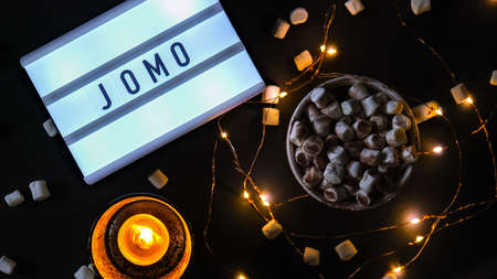 Lightbox with text JOMO Joy of Missing Out. The concept of relaxation from information and gadgets. Top view. Flat lay. Cup with cacao and marshmallows. Digital detox