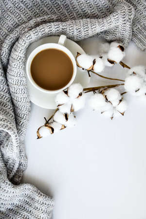 Cup of coffee with cotton plant cinnamon sticks and anise star on white background. Sweater around. Winter morning routine. Coffee break. Copy space. Top view. Breakfast. Flat lay
