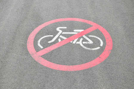Bicycle riding prohibited symbol on tarred road. cycling forbidden sign printed on the ground on asphalt. 스톡 콘텐츠