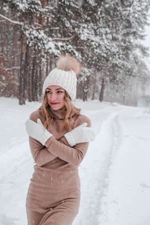 Christmas, holidays and season concept. Young happy woman blowing snow in the winter forest nature. Warm clothing knitted gloves and hat. Winter forest landscape background