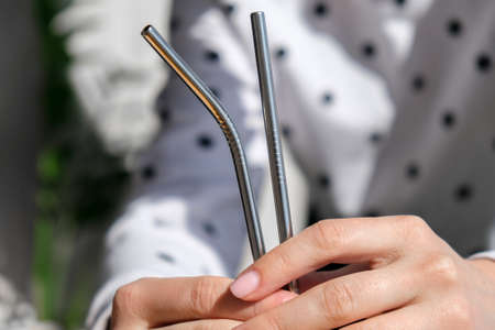 Woman holding Reusable Metal Straw. Female Hand on reusable collapsible drinking straw. Eco lifestyle and zero waste concept. Plastic free Stock fotó