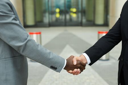 Close-up of multi ethnic business people shaking hands while standing outdoors in the city 写真素材
