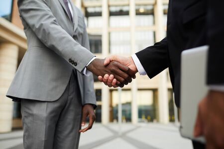 Close-up of multiethnic business people in suits standing and shaking hands they greeting each other before meeting outdoors 写真素材