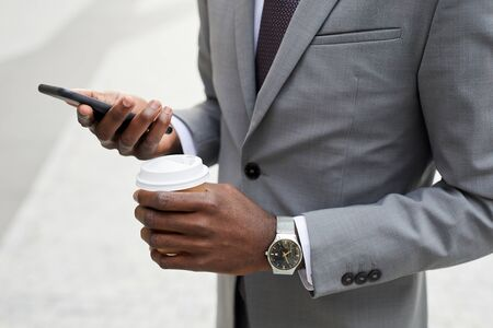 Close-up of African businessman in suit holding cup of coffee and using mobile phone for his online work outdoors Banco de Imagens