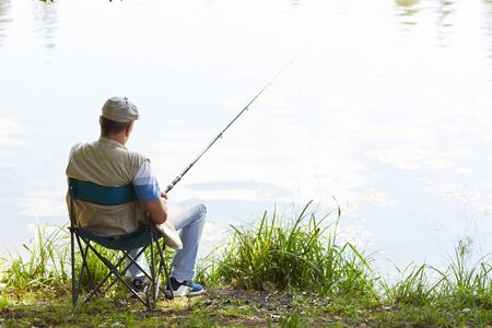 Rear view of mature fisherman sitting on chair with fishing rod and waiting for a catch at the lakeside outdoors Banco de Imagens
