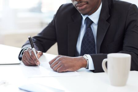 Close-up of African businessman sitting at office desk holding pen and signing a business contract