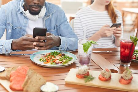 Close-up of African young man sitting at the table and taking a picture of his meal on mobile phone during lunch with his friends