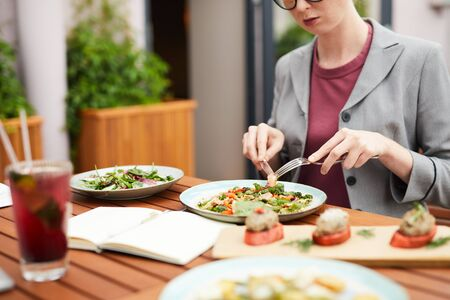 Close-up of young woman sitting at the table and eating vegetable salad during her business lunch in outdoor cafe