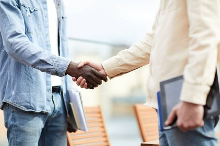 Close-up of two multiethnic business partners standing and shaking hands they greeting each other during a meeting