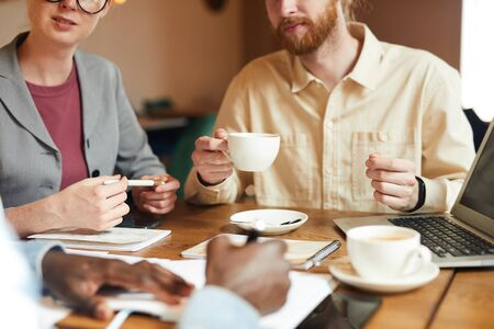Close-up of business people sitting at the table and drinking coffee while their colleague signing a business document they have a business meeting Zdjęcie Seryjne