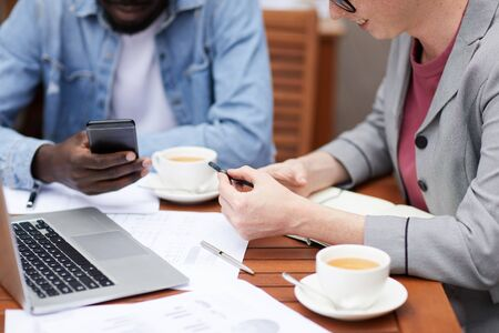 Close-up of business colleagues sitting at the table with laptop and documents drinking coffee and using their mobile phones for work in cafe Zdjęcie Seryjne