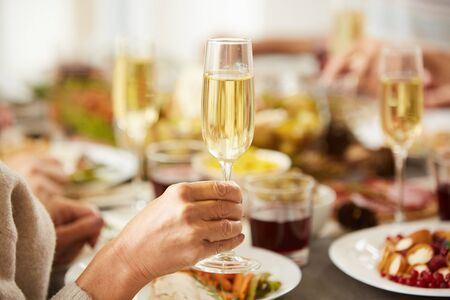 Close-up of female hand holding glass with champagne while have dinner at the table 版權商用圖片