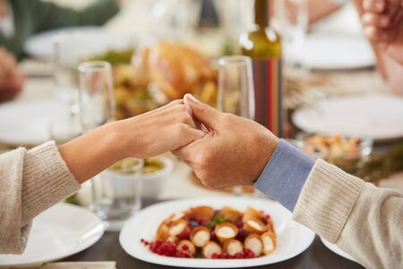 Close-up of senior couple holding hands while sitting at dining table and eating during dinner party Stock Photo