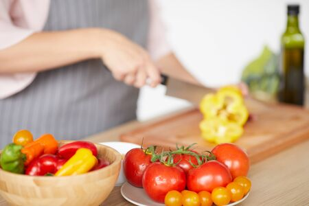 Close-up of woman standing at the table and cutting pepper on cutting board for vegetable salad Stock Photo