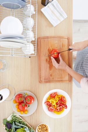 High angle view of young woman standing and cutting tomato on cutting board for vegetable salad in the kitchen