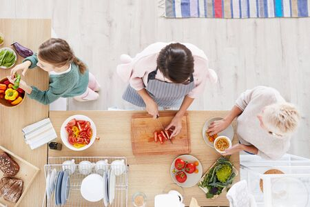 High angle view of family of three standing at the kitchen table and preparing food for dinner together in the kitchen