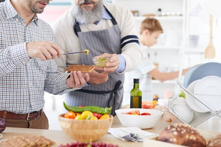 Close-up of young man standing and tasting sauce giving by the mature man while they preparing food in the kitchen Stock Photo