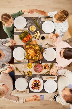 High angle view of family sitting at the table holding hands and praying before the meal they celebrating Thanksgiving Day