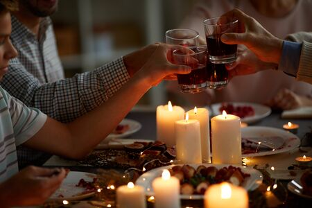 Close-up of family sitting at dining table with candles and toasting with glasses of wine in the evening at home Stock Photo