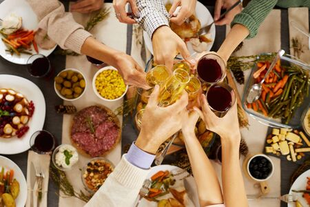High angle view of people toasting with glasses of champagne and wine at the table while celebrating Thanksgiving Day