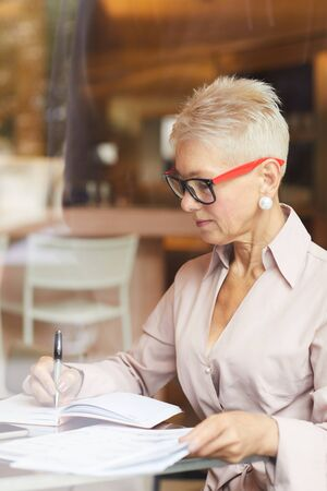 Concentrated mature businesswoman with blond short hair wearing eyeglasses sitting at the table and writing something in documents in cafe