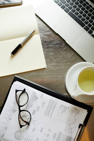 High angle view of documents with financial charts cup of tea and laptop on the table Stok Fotoğraf