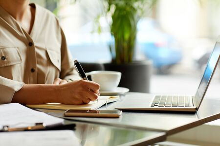 Close-up of woman sitting at the table in front of laptop and making notes in her notepad while drinking coffee
