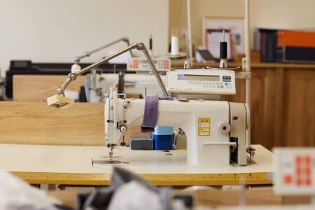 Image of sewing workshop with sewing machines on the tables ready for work