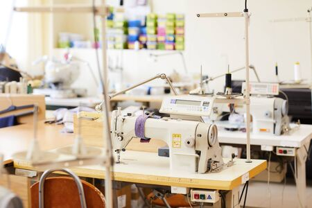 Image of modern sewing machines on work places in workshop