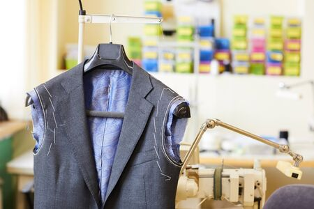 Image of male jacket hanging on the rack in workshop its sewing for future male suit
