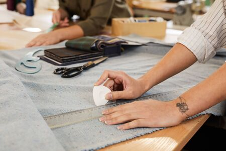 Close-up of tailor holding chalk and drawing pattern with ruler on fabric for future dress at the table in atelier