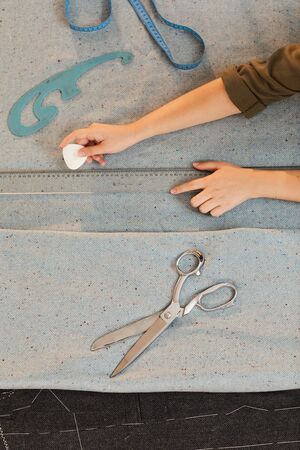 Close-up of hands of tailor using chalk and ruler and drawing pattern on fabric at the table