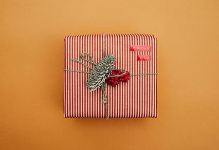 Close-up of Christmas gift box decorated with fir branch and red berries wrapped in striped wrapping paper isolated on yellow background Stock fotó