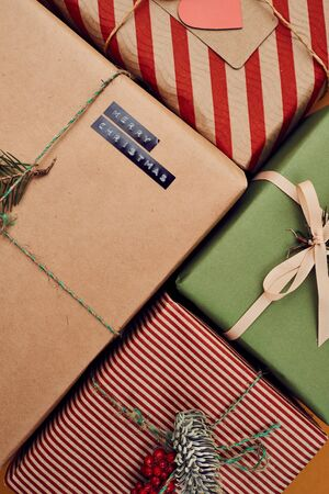 Close-up of decorated gift boxes wrapped in colorful wrapping paper made for Christmas