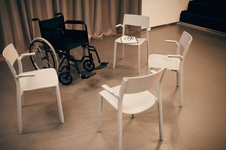 Image of empty room with white chairs and wheelchair prepared for meeting Stockfoto