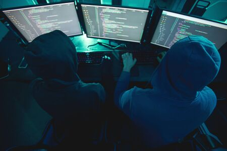 Rear view of two computer hackers in hoodies typing on keyboard and breaking the computer system while sitting in dark office