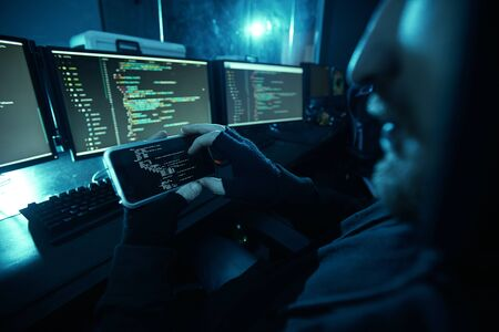 Close-up of computer hacker looking at computer monitor and guessing the password using his mobile phone in dark room Фото со стока