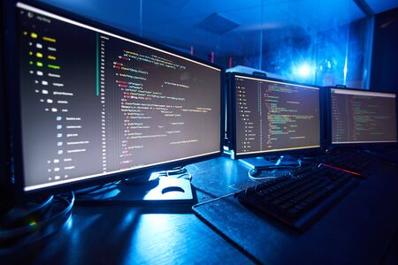 Image of computer monitors updating the software they standing on the table in dark room Фото со стока