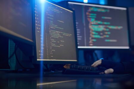 Image of computer monitors with software standing on the table in dark office