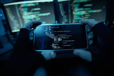 Close-up of computer hacker in black gloves holding his mobile phone and installing the new software on it in dark room