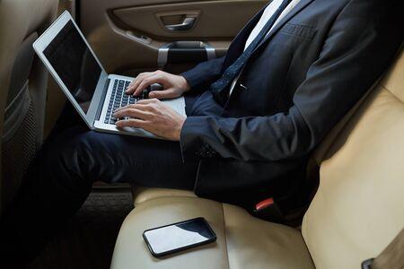 Primo piano dell'uomo d'affari in tuta seduto sul sedile posteriore di un'auto di lusso e digitando sul computer portatile che lavora online durante la guida Archivio Fotografico