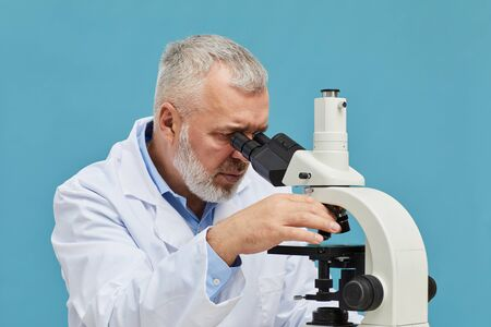 Mature scientist in white coat looking through the microscope isolated on blue background
