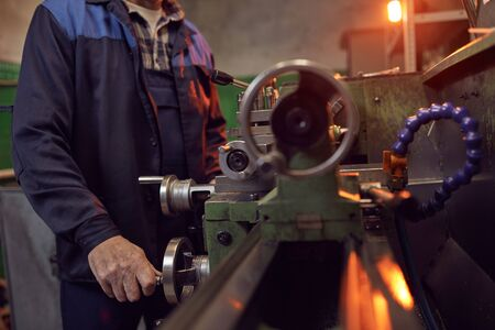 Close-up of manual worker in special clothing working on lathe in the plant
