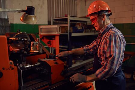 Mature engineer in protective eyesglasses and in work helmet standing near the machine and controlling it in the plant Banque d'images