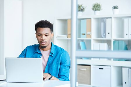 Serious African office worker in casual clothing working online on laptop while sitting at his workplace at office