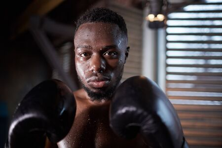 Portrait of African young sportsman in boxing gloves looking at camera during training in gym