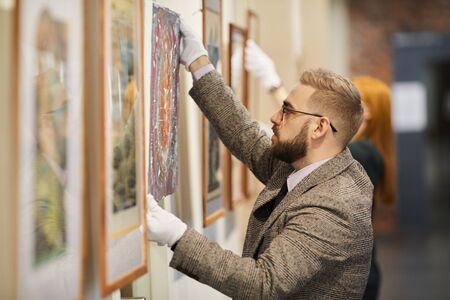 Handsome bearded man in eyeglasses and in suit hanging the picture on the wall and preparing for the art exhibition together wth woman